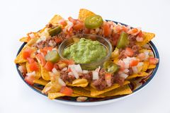Mexican nachos with beef, guacamole, cheese sauce, peppers, tomato and onion in plate isolated royalty free stock image