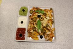 Mexican nachos with chicken. Nachos with corn chips, cheese, salsa, guacamole, sour cream, and chicken. A plate of tortilla nachos stock image