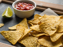 Mexican nachos chips  with salsa sauce and lime slice Stock Images