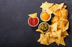 Mexican nachos corn chips with guacamole, salsa and cheese dip. On dark background royalty free stock photos