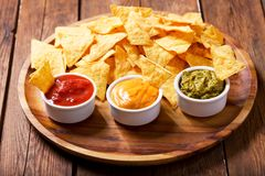 Mexican nachos corn chips with guacamole, salsa and cheese dip. On wooden table royalty free stock image