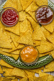 Mexican nachos on a green plate with different sauces top view close up Royalty Free Stock Photos