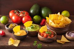 Mexican nachos with guacamole, salsa and cheese dip stock image