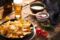 Mexican nachos served with cheese, variety of dips, beer, chilly, tomatoes, rustic wooden table stock photography