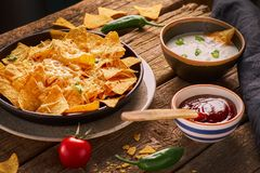 Mexican nachos served with melted cheese, variety of dips, chilly, tomatoes, rustic wooden table royalty free stock image