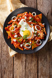 Mexican nachos with tomato salsa, chicken and egg close-up. Vert. Mexican nachos with tomato salsa, chicken and egg close-up on a plate. Vertical view from above stock photography