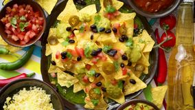 Mexican nachos tortilla chips with black bean, jalapeno, guacamole. Tomatoes salsa, cheese and botteled beer. Placed on a table stock video footage
