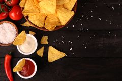 Mexican nachos in Wooden Bowl tortilla chips with chilli sauce, salsa and cheese dip, top view and Black Background. Mexican nachos in Wooden Bowl tortilla chips stock photos