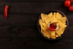 Mexican nachos in Wooden Bowl tortilla chips with chilli sauce, salsa and cheese dip, top view and Black Background. Mexican nachos in Wooden Bowl tortilla chips stock photography