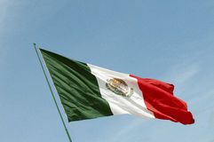 Mexican National Flag waving against a blue sky. A Mexican flag flapping in the wind against a blue sky background Royalty Free Stock Images