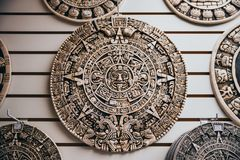 Mexican ornament of the Aztec sun god disk. Hanging in the wall of a store for tourists royalty free stock photography
