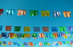 Mexican paper bunting decoration celebratory flags against blue sky. Traditional mexican paper bunting decoration celebratory flags against blue sky Royalty Free Stock Photography