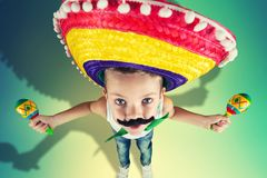 Mexican party.Boy with a fake mustache in a sombrero playing the maracas. Boy with a fake mustache in a sombrero playing the maracas.Mexican party royalty free stock image