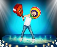 Mexican party. Boy in sombrero with a guitar on stage.Mexican macho. Mexican macho.Mexican party. Boy in sombrero with a guitar on stage stock photography