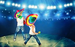 Mexican party. Two brothers in sombreros perform on stage, sing serenades. Two brothers in sombreros perform on stage, sing serenades.Mexican party stock photo