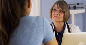 Mexican patient talking to Senior doctor in office Stock Photography
