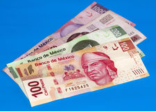 Mexican Peso Bills Over Blue Canvas. New 100, 200, 500 and 1000 peso mexican bills over a blue canvas background for contrast Royalty Free Stock Image