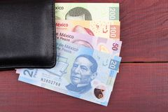 Mexican Pesos in the black wallet. On a wooden background Stock Photos