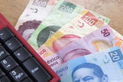 Mexican Pesos. Money, coins and bills mexican pesos a pen and a number keypad over a wooden table Royalty Free Stock Photography