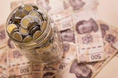 Mexican pesos savings. Mexican pesos banknotes and coins in glass jar Royalty Free Stock Photos