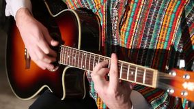 Mexican plays guitar Close-up plan, Playing guitar. A Mexican plays the guitar while sitting on a chair indoors. You can apply for entertainment and music videos stock video footage