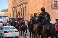 Mexican police on horse patrol at Festival. Zacatecas, Mexico, 02 August 2013: Mexican police with guns on horses patrol the colonial center at the 18th Festival Royalty Free Stock Image