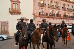 Mexican police on horse patrol at Festival. Zacatecas, Mexico, 02 August 2013: Mexican police with guns on horses patrol the colonial center at the 18th Festival Stock Images