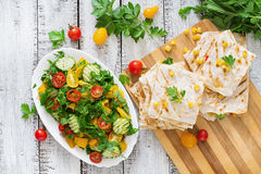 Mexican Quesadilla wrap with chicken, corn and sweet pepper and fresh salad. Top view Royalty Free Stock Photo