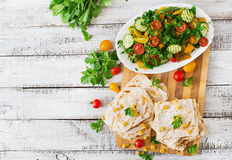 Mexican Quesadilla wrap with chicken, corn and sweet pepper and fresh salad. Top view Stock Photos