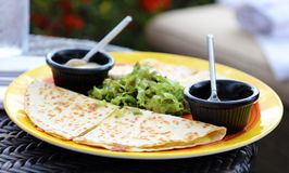 Mexican quesadillas dinner with chicken steak and queso. Avocado y salsa Stock Image