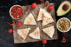 Mexican quesadillas with salsa nad guacamole. Mexican quesadillas, cheese filled tortilla slices wit salsa and guacamole Stock Images
