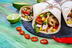 Mexican restaurant fast food - wrapped burritos with pork meat, mushrooms and vegetables closeup at wooden desk. Mexican burritos. Cooking recipe stock photos