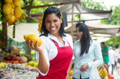 Mexican saleswoman on a farmers market selling fresh fruits. With tropical fruits in the background royalty free stock photography