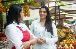 Mexican saleswoman on a farmers market talking with client. With tropical fruits in the background stock photo