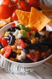Mexican salsa with black beans and corn chips close up. Vertical Royalty Free Stock Image