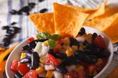 Mexican salsa with black beans and corn chips nachos macro. hori Royalty Free Stock Photo