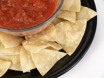 Mexican Salsa Platter. Black plate full of corn tortilla chips, surrounding a bowl of Mexican salsa Royalty Free Stock Photo