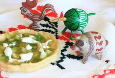 Mexican Salsa Verde Gordita and clay animals. Typical Mexican salsa verde or green tomatillo sauce on a gordita with cream Royalty Free Stock Images