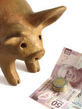 Mexican savings. Mexican handmade piggy bank with Mexican pesos bills and coins Stock Image