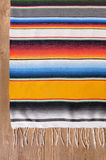Mexican serape blanket background copy space vertical. Mexican background with traditional serape blanket or rug on a wood floor.  Space for copy Stock Images