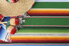 Mexican sombrero background copy space. Mexican background with sombrero straw hat, maracas and traditional serape blanket or rug.  Space for copy Stock Images