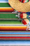 Mexico : Mexican sombrero and blanket background, copy space vertical. Mexican background with sombrero straw hat, maracas and traditional serape blanket or rug Stock Photo
