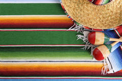 Mexico, Mexican sombrero blanket background, copy space. Mexican background with sombrero straw hat, maracas and traditional serape blanket or rug.  Space for Royalty Free Stock Photos