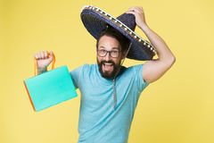 Mexican shopping. Man smiling face in sombrero hat shopping yellow background. Guy with beard looks festive in sombrero. Holiday sales concept. Man in festive royalty free stock photos
