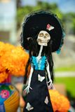Mexican skeleton figure in national headdress and blue and black dress isolated on the background of a bouquet of orange flowers. Mexican skeleton figure, in royalty free stock images