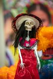 Mexican skeleton figure in national headdress and red dress isolated on the background of a bouquet of orange flowers. Mexican skeleton figure, in national royalty free stock images