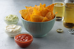 Mexican snack tortilla in blue bowl with dip sauces and beer on the table. Crusty nachos in a bowl. Concept of junk food Stock Images