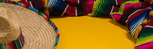 Mexican Sobrero and Serape blanket on yellow background with cop. A traditional Mexican Sombrero and serape blanket on a yellow background with copy space Stock Images
