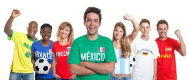 Mexican soccer supporter with crossed arms and fans from other c stock photo
