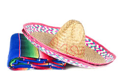Mexican Sombrero. Straw Mexican sombrero and a colorful rug isolated on white Royalty Free Stock Photography